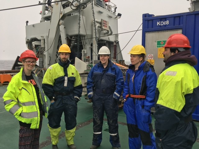 A photo of the AKMA team stood on the research vessel while at sea.