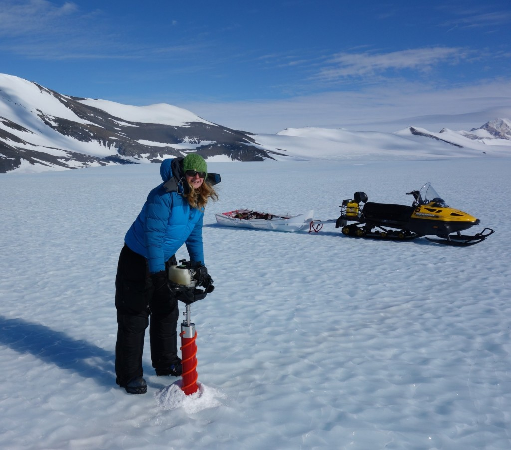 Drilling using a Kovacs corer. Here I'm wearing 3 coats: a light down jacket, a soft windproof shell, and my big down jacket on the top. I'm also wearing down trousers over my salopettes. It's quite windy on the blue ice, so it can feel very cold. (Credit: H. Millman)
