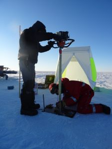 Drilling a firn core requires patience, focus and sturdy gloves. Credit: Anna Winter.