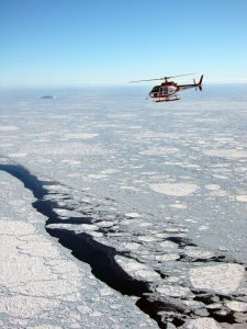 An aerial view of the helicopter taking data of the sea ice below.