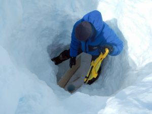 E. Bagshaw testing the range of an ETracer in a 12m borehole at the bottom of a 2m deep snow pit. [Credit: N. B. Karlsson].