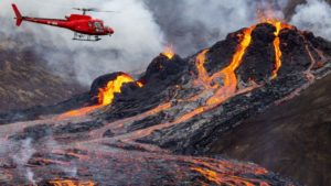 A volacno erupts with bright red and orange magma flowing down it's sides and a helicopter flies by to survey the scene.