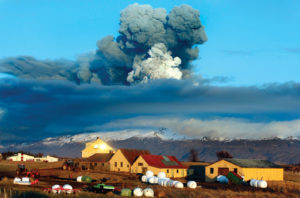 In the foreground there is a farm with a backdrop of a volcano is emitting large amounts of ash into the air.