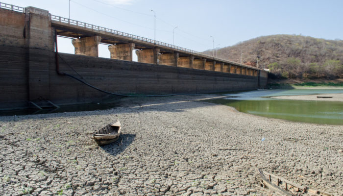 A dam, an almost empty water reservoir and a small abandoned boat