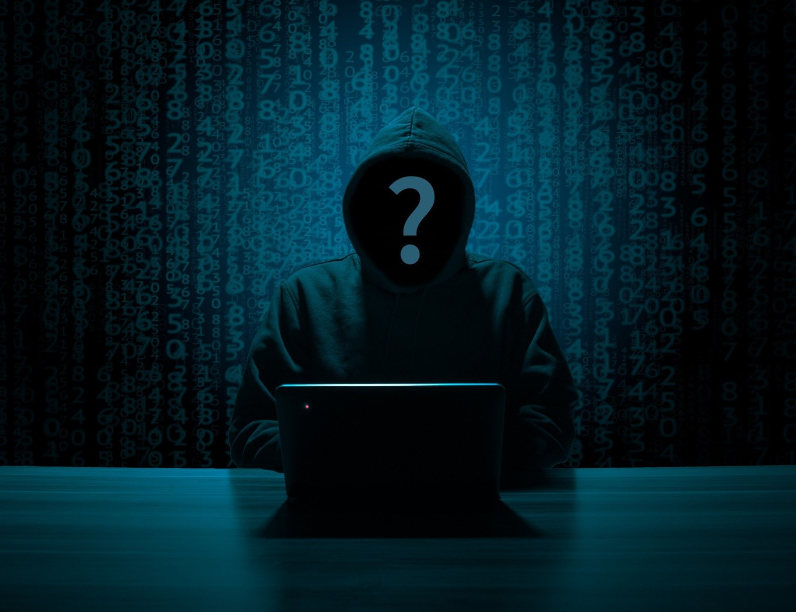 An image of someone wearing a black hoodie behind a laptop, with a question mark over their face.