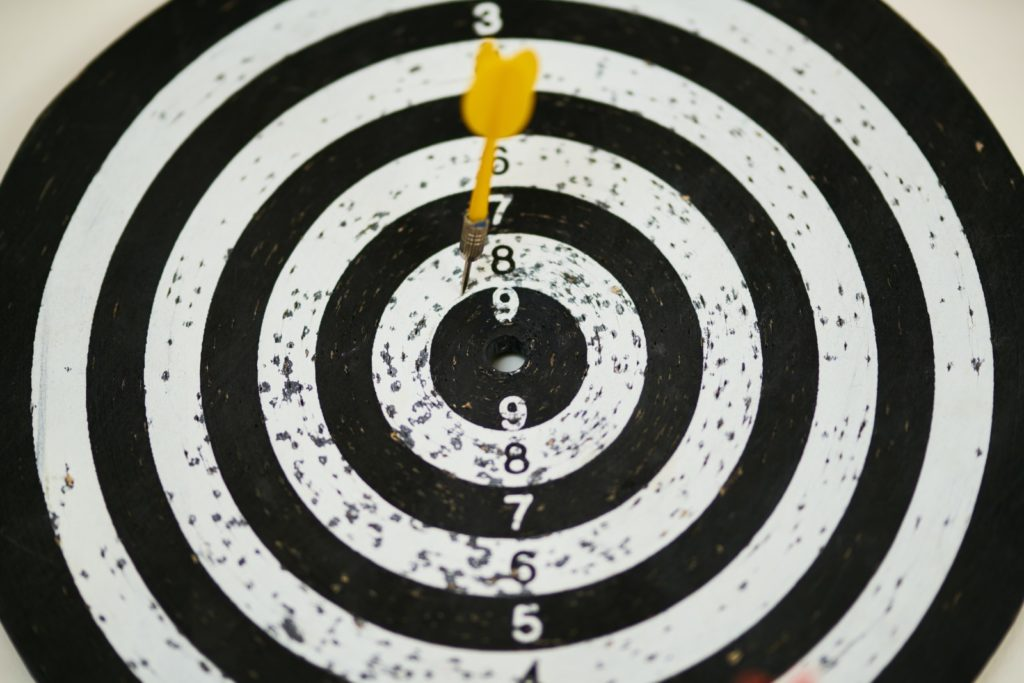 Black and white aim with a yellow dart arrow.