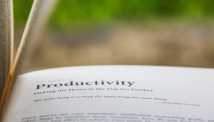 Photo from the page of a book, with an out of focus green background. The text on the page reads: 'Productivity, making the hours in the day go further. The main thing is to keep the main thing the main thing - Steven Covey'.