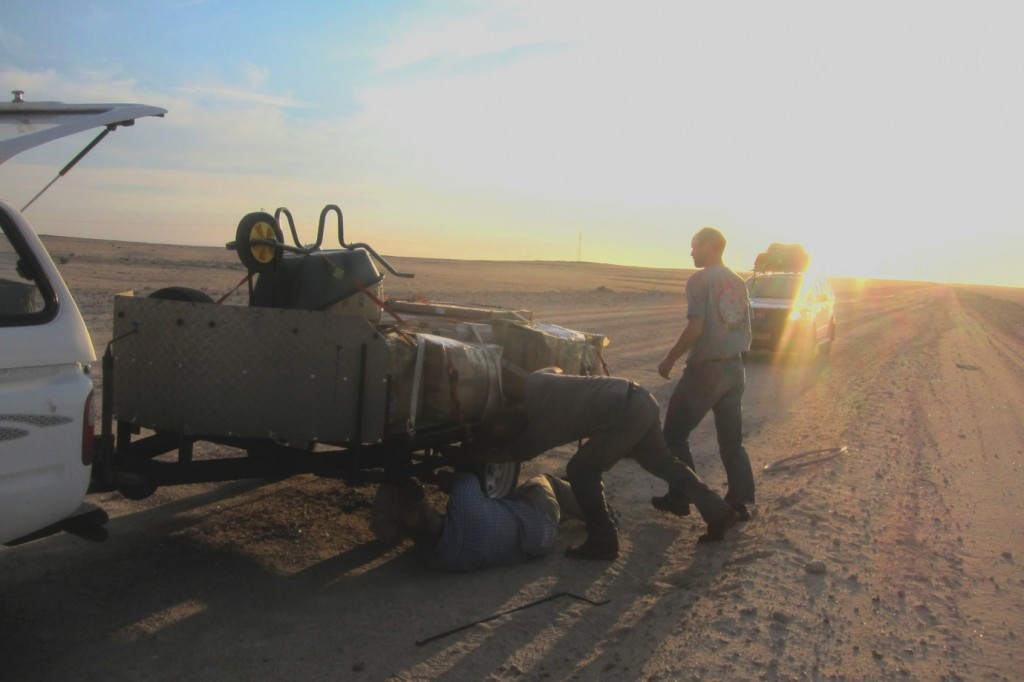 Trailer repair at sunset with a ratchet strap, a jack, and a socket extension. (Credit: A. Dansie)