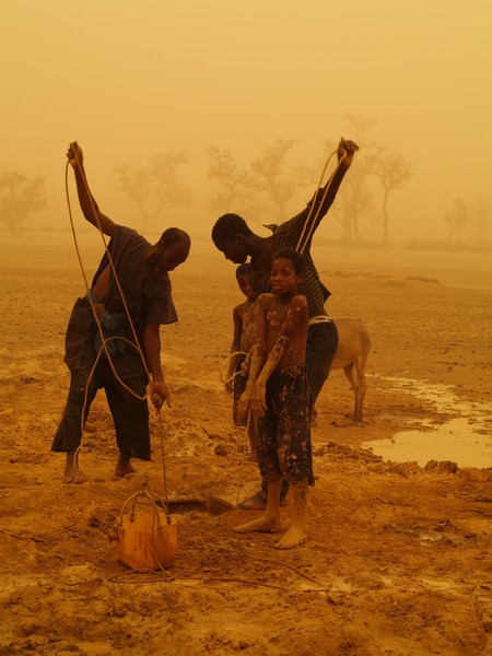 Men and children drawing water for irrigation during a sandstorm. (Credit: Velio Coviello via imaggeo.egu.eu)