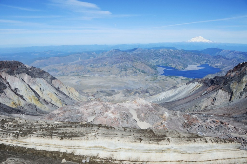 The view down over Mount St. Helens crater from the summit, in the centre the lava dome has grown in the collapse scar from the 1980 eruption. The collapse devastated the proximal land and vegetation, dead trees still float like matchsticks in the calm waters of Spirit Lake and the event left the inner workings of the volcano open to scrutiny. In the background, the glacier-capped Mount Rainier lies dormant. (Credit: Jackie Kendrick)
