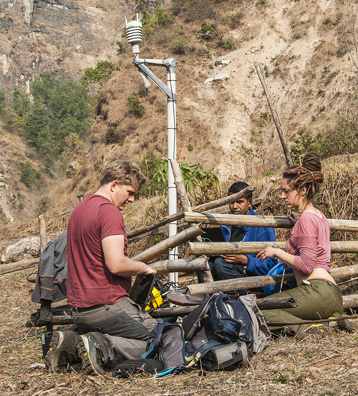 Christoff Andermann, Camilla Brunello and Bhairab Sitaula performing maintenance on a broadband seismometer and weather station near the village of Chaku on the Arniko Highway (Credit: Jane Qiu)