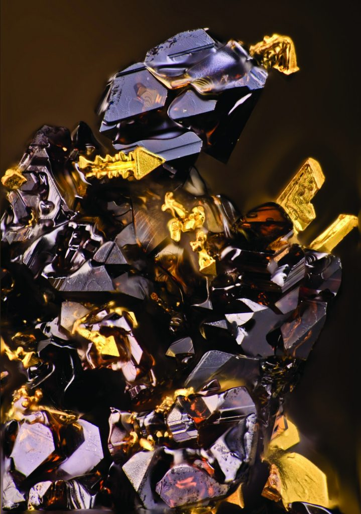 "Sphalerite's ""Transformer""'. Credit: Dmitry Tonkacheev (distributed via imaggeo.egu.eu). The bulk of Au wire ""boards"" on the dark-brown phase surface in the form of fascination crystals (usually arborescent). Some of them look like a weapon from the ""Transformers"" arsenal or parts of his armor. Also bright diamond luster of this creature makes our ""Knight"" even more ultra-modern."