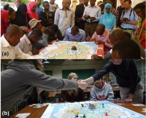 (a) Game session organized with citizens in Moroni (Comoros Islands). (b) Interaction among Belgian students to develop a resilient community. Taken from Mossoux, S., et al. (2016)