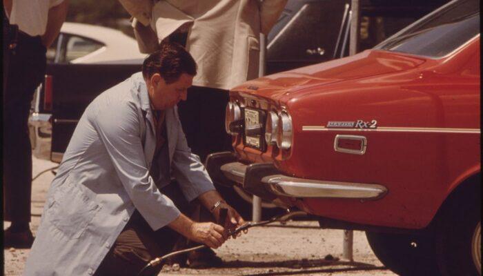 Inspector testing vehicle emissions