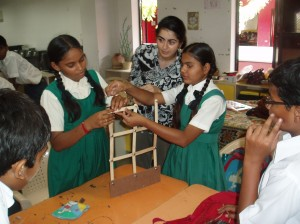 Solmaz during a public engagement activity at a school in Gujarat, India. School children are tought to build and test a wall model on a shake table as part of a  earthquake education workshop.  Image courtesy of Solmaz Mohadjer.