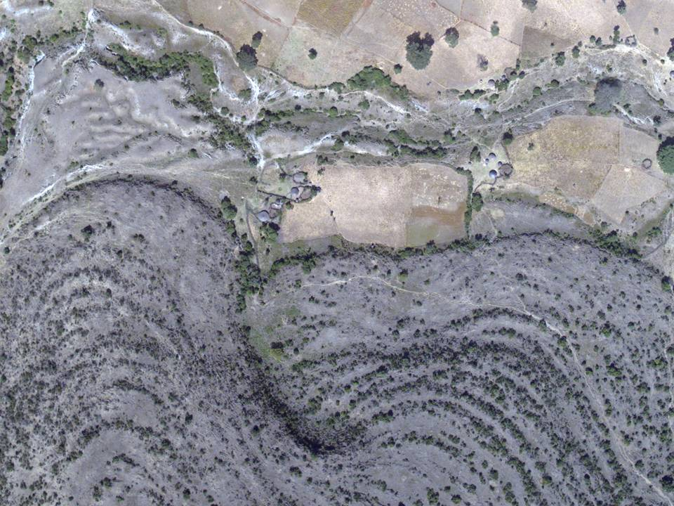 Aerial view of a young lava flow spilling into the central crater of Alutu volcano, Ethiopia. Note the trees and houses for scale.